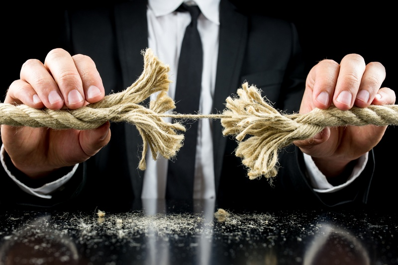 Businessman holding a frayed rope with one remaining string intact in both his hands in a risk and adversity concept. Over black background.
