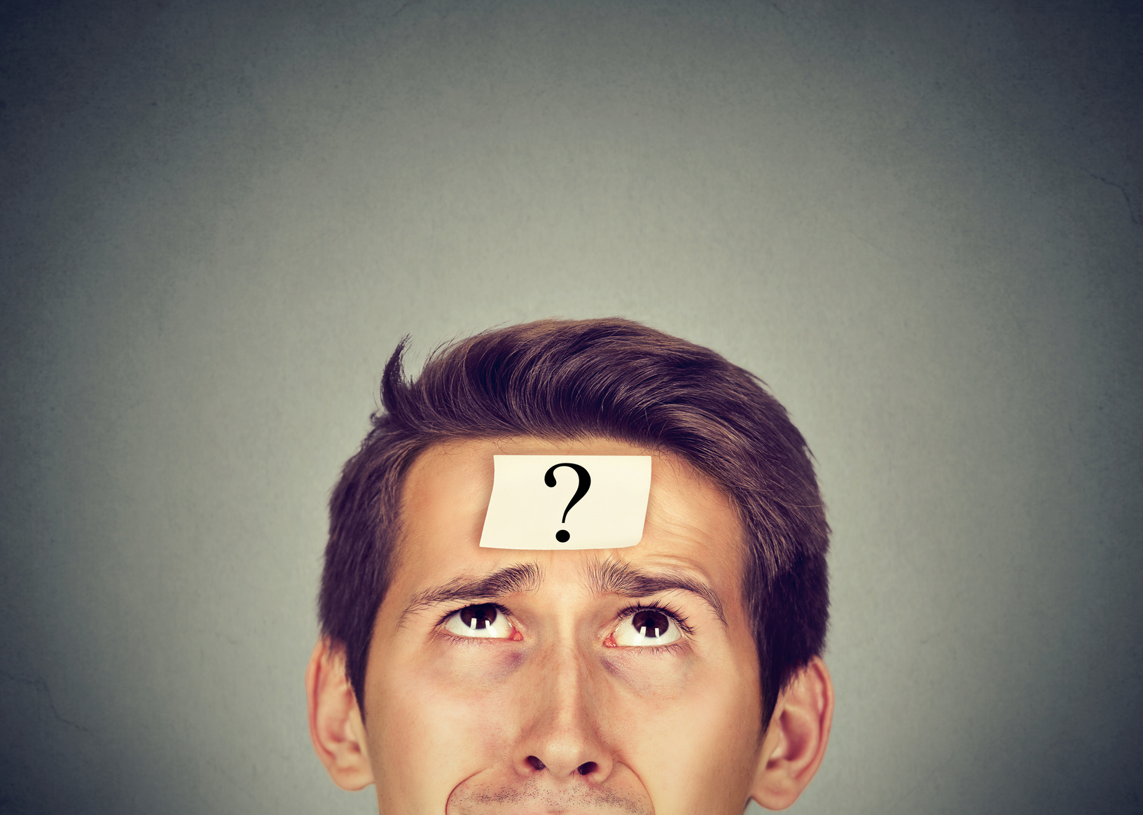 thinking man with question mark on gray wall background