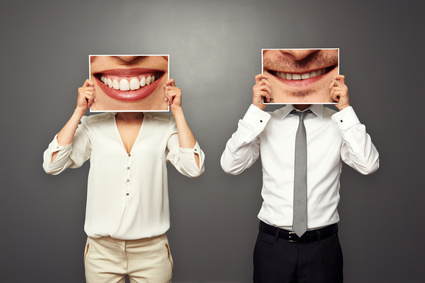 woman and man holding pictures with big smile. concept photo over dark background